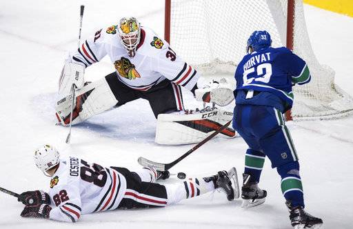 Vancouver Canucks' Bo Horvat, right, has his shot blocked by Chicago Blackhawks' Jordan Oesterle in front of goalie Anton Forsberg, of Sweden, during the second period of an NHL hockey game Thursday, Feb. 1, 2018, in Vancouver, British Columbia. (Darryl Dyck/The Canadian Press via AP)