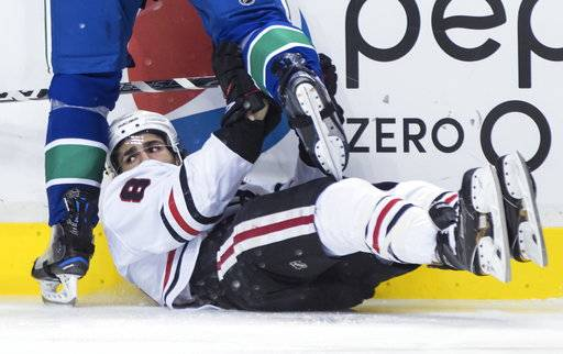 Chicago Blackhawks' Nick Schmaltz falls to the ice under Vancouver Canucks' Brandon Sutter during the first period of an NHL hockey game Thursday, Feb. 1, 2018, in Vancouver, British Columbia. (Darryl Dyck/The Canadian Press via AP)