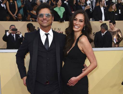 FILE - In this Jan. 21, 2018 file photo, John Stamos, left, and Caitlin McHugh arrive at the 24th annual Screen Actors Guild Awards at the Shrine Auditorium & Expo Hall  in Los Angeles. Police say burglars stole $165,000 in jewelry from a room at the Beverly Hills Hotel that was occupied by McHugh.  A police statement says Caitlin McHugh was away from her room Friday, Feb. 2, when a crook or crooks got in and took several items of jewelry. It's unclear how the burglars got inside. There's no indication of forced entry.(Photo by Jordan Strauss/Invision/AP, File)