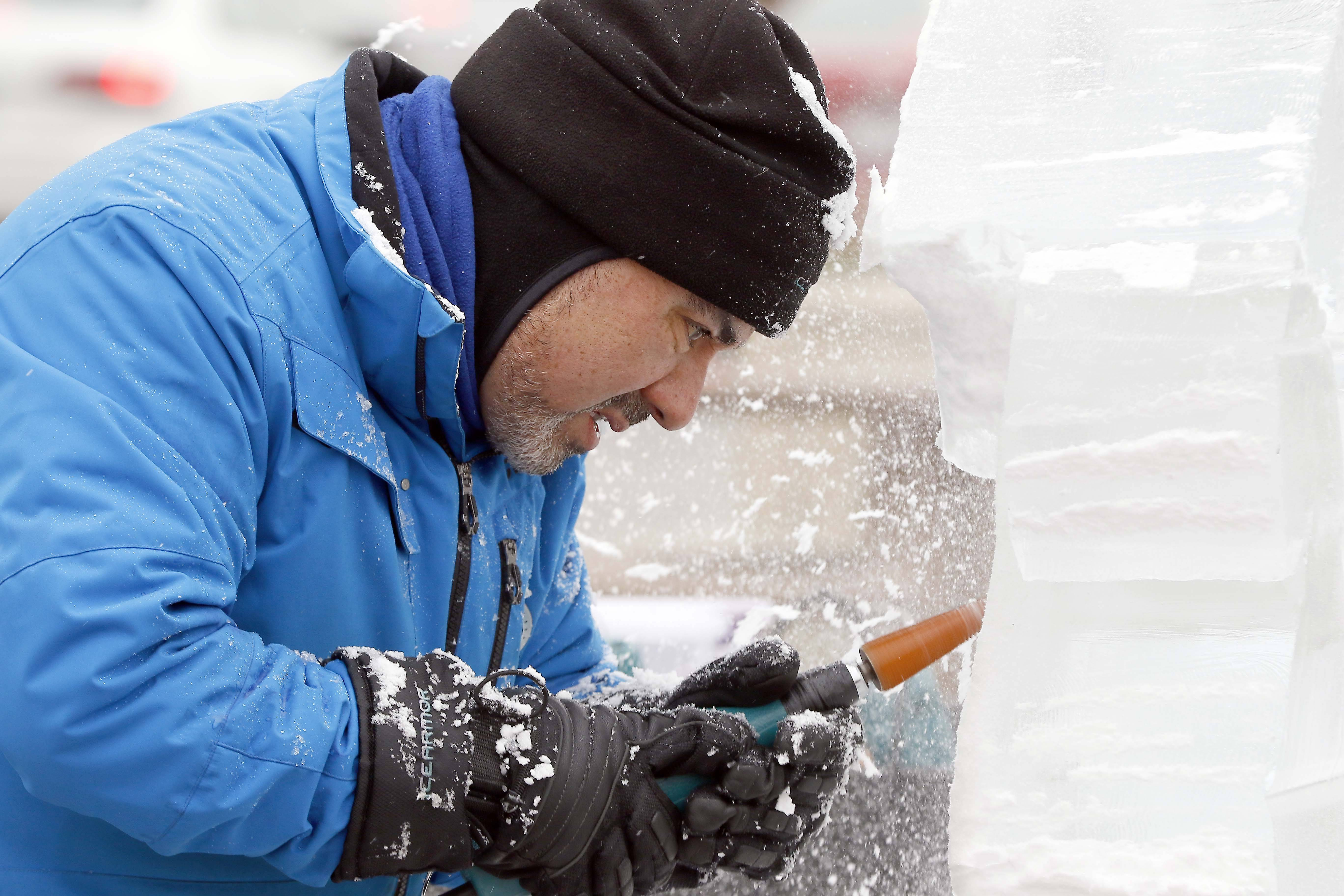 Jim Bringas of Chicago Ice Works carves a dragon Saturday during the Ice (Cubed) Festival in downtown Wheaton. He said this sculpture should take him about an hour and a half to complete. Bringas has been carving ice for more than 25 years.