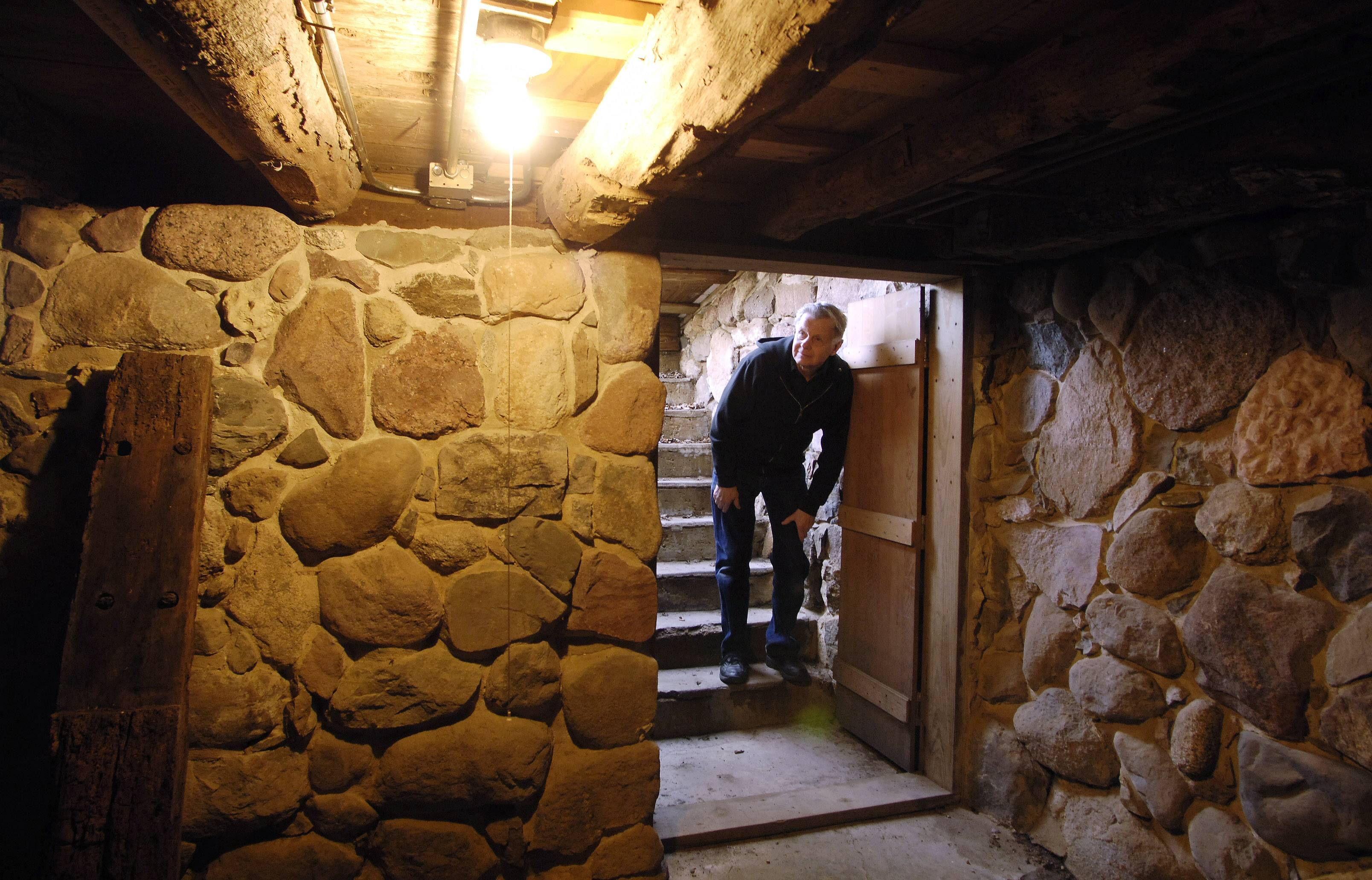 Tom Mellen peeks into the cellar on the Mother Rudd Home in Gurnee where slaves escaping to freedom in Canada via the Underground Railroad reportedly took shelter on the way.