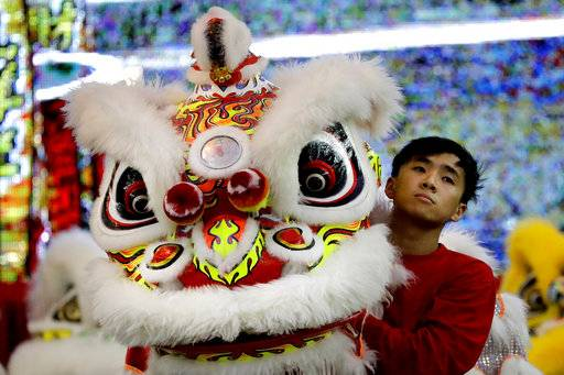 CORRECTS TO TROUPE - In this Friday, Feb. 2, 2018, photo, a member of a lion dance troupe from Hong Kong waits to compete in the 11th International Lion Dance Competition in Singapore. This lion dace competition is usually held in a lead up to the Chinese Lunar New Year celebrated in Singapore. Lion dance is a traditional dance in Chinese culture and some other Asian countries in which performers from a lion dance troupe will mimic a lion's movements while dressed in a lion's costume. This is believed to bring fortune and luck. These performers from Vietnam, Singapore, Myanmar, Indonesia, Hong Kong, Taiwan and Malaysia gathered in Singapore to compete against one another and are judged on their skill, grace and musicality amongst other things.