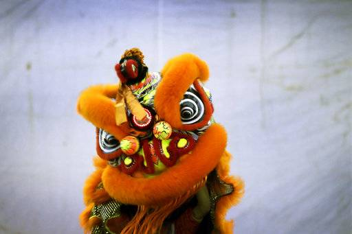 CORRECTS TO TROUPE - In this Friday, Feb. 2, 2018, photo, members of a lion dance troupe from Singapore compete in the 11th International Lion Dance Competition in Singapore. This lion dace competition is usually held in a lead up to the Chinese Lunar New Year celebrated in Singapore. Lion dance is a traditional dance in Chinese culture and some other Asian countries in which performers from a lion dance troupe will mimic a lion's movements while dressed in a lion's costume. This is believed to bring fortune and luck. These performers from Vietnam, Singapore, Myanmar, Indonesia, Hong Kong, Taiwan and Malaysia gathered in Singapore to compete against one another and are judged on their skill, grace and musicality amongst other things.