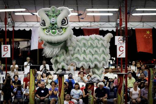 CORRECTS TO TROUPE - In this Friday, Feb. 2, 2018, photo, spectators watch as members of a lion dance troupe from Indonesia compete in the 11th International Lion Dance Competition in Singapore. This lion dace competition is usually held in a lead up to the Chinese Lunar New Year celebrated in Singapore. Lion dance is a traditional dance in Chinese culture and some other Asian countries in which performers from a lion dance troupe will mimic a lion's movements while dressed in a lion's costume. This is believed to bring fortune and luck. These performers from Vietnam, Singapore, Myanmar, Indonesia, Hong Kong, Taiwan and Malaysia gathered in Singapore to compete against one another and are judged on their skill, grace and musicality amongst other things.