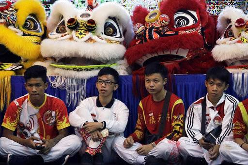 CORRECTS TO TROUPE - In this Friday, Feb. 2, 2018, photo, competitors sit in front of lion costumes as they watch fellow competitors perform during the 11th International Lion Dance Competition in Singapore. This lion dace competition is usually held in a lead up to the Chinese Lunar New Year celebrated in Singapore. Lion dance is a traditional dance in Chinese culture and some other Asian countries in which performers from a lion dance troupe will mimic a lion's movements while dressed in a lion's costume. This is believed to bring fortune and luck. These performers from Vietnam, Singapore, Myanmar, Indonesia, Hong Kong, Taiwan and Malaysia gathered in Singapore to compete against one another and are judged on their skill, grace and musicality amongst other things.