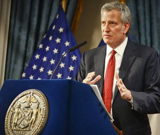 FILE- In this Feb. 1, 2018 file photo, New York City Mayor Bill de Blasio speaks as he presents his preliminary budget during a news conference at City Hall in New York. De Blasio put his legal troubles behind him a year ago when federal prosecutors said he wouldn't face criminal charges over his campaign fundraising tactics. Recently, new revelations that two businessmen pleaded guilty to making donations that amounted to bribes has led to a renewed round of criticism of the Democrat.