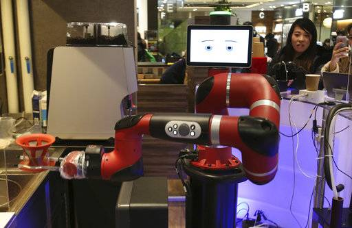 "Robot barista named ""Sawyer"" makes a coffee at Henn-na Cafe, Japanese meaning ""Strange Cafe""in Tokyo, Friday, Feb. 2, 2018. The cafe's robot barista brews and serves coffee as the rapidly aging country seeks to adapt to shrinking workforce. The arm robot ""Sawyer"" debuted this week in Tokyo's downtown business and shopping district of Shibuya."