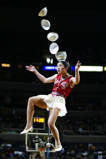 FILE - In this March 7, 2004 file photo, Rong Niu of China performs during the halftime break of the New York Knicks-Washington Wizards game by tossing the bowls with her right foot and catching them with her head as she balances on a unicycle in Washington. Someone at the San Francisco airport stole a 7-foot unicycle used by the Red Panda Acrobat for her plate-juggling routine and the legendary performer is offering a $2,000 reward to get it back. Police on Wednesday, Jan. 31, 2018, released surveillance photos from Jan. 24 that show a man wheeling away a black bag containing the $25,000 unicycle belonging to acrobat Rong Niu.