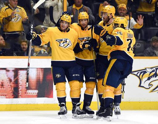 Nashville Predators left wing Kevin Fiala (22) is congratulated by teammates Craig Smith (15), Mattias Ekholm (14) and P.K. Subban (76) after his goal in the second period against the New York Rangers of an NHL hockey game Saturday, Feb. 3, 2018, in Nashville, Tenn. (George Walker IV/The Tennessean via AP)