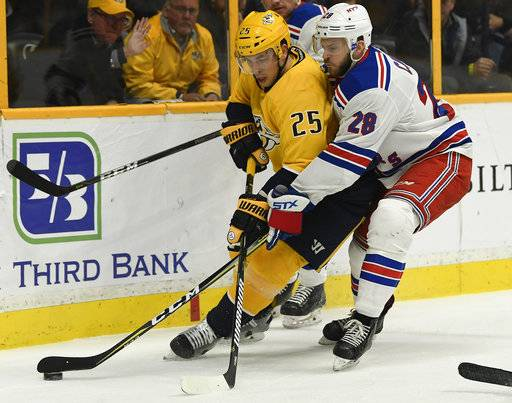 Nashville Predators defenseman Alexei Emelin (25) tries to get the puck past New York Rangers center Paul Carey (28) in the first period of an NHL hockey game Saturday, Feb. 3, 2018, in Nashville, Tenn. (George Walker IV/The Tennessean via AP)