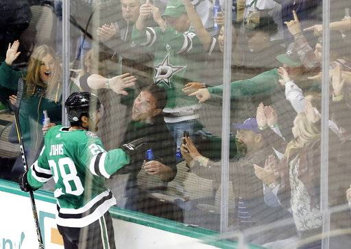 Dallas Stars defenseman Stephen Johns (28) celebrates with fans after scoring a goal during the second period of an NHL hockey game against the Minnesota Wild Saturday, Feb. 3, 2018, in Dallas.