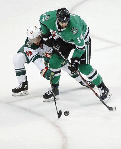 Minnesota Wild defenseman Jared Spurgeon (46) battles Dallas Stars forward Jamie Benn (14) for the puck during the first period of an NHL hockey game Saturday, Feb. 3, 2018, in Dallas.
