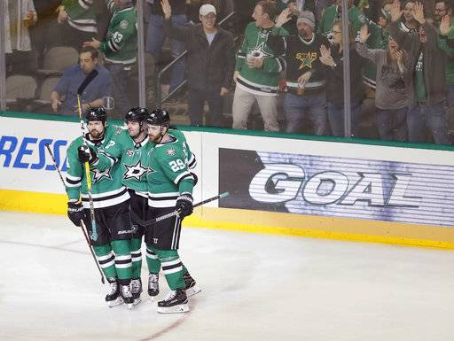 Dallas Stars forward Alexander Radulov, middle, is congratulated by forward Jamie Benn, left, and defenseman Greg Pateryn after scoring a goal against the Minnesota Wild during the third period of an NHL hockey game Saturday, Feb. 3, 2018, in Dallas. Dallas won 6-1.