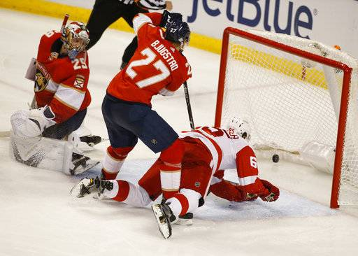 Detroit Red Wings defenseman Danny DeKeyser, right, scores against Florida Panthers goaltender Harri Sateri (29) and center Nick Bjugstad (27) during the third period of an NHL hockey game, Saturday, Feb. 3, 2018 in Sunrise, Fla. The Panthers defeated the Red Wings 3-2.