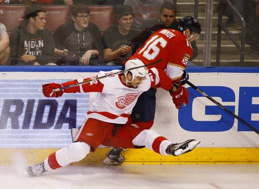 Detroit Red Wings defenseman Jonathan Ericsson, foreground, and Florida Panthers center Aleksander Barkov (16) battle for the puck during the second period of an NHL hockey game, Saturday, Feb. 3, 2018 in Sunrise, Fla.