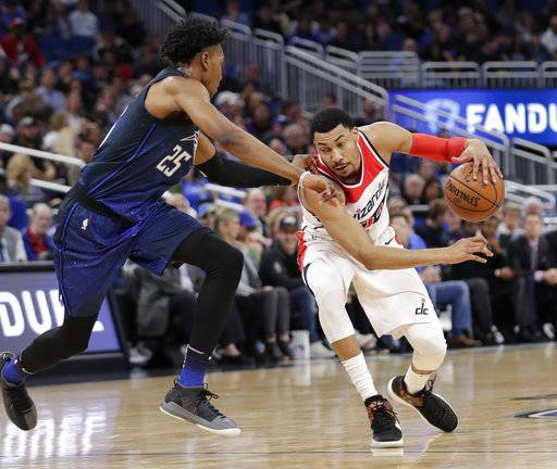 Washington Wizards' Otto Porter Jr., right, drives past Orlando Magic's Wesley Iwundu (25) during the first half of an NBA basketball game Saturday, Feb. 3, 2018, in Orlando, Fla.