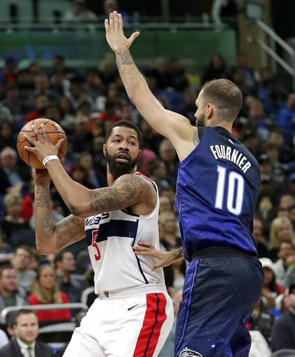 Washington Wizards' Markieff Morris, left, looks to pass the ball around Orlando Magic's Evan Fournier (10) during the first half of an NBA basketball game Saturday, Feb. 3, 2018, in Orlando, Fla.