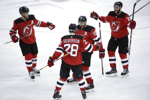 New Jersey Devils, from left, Taylor Hall, Damon Severson (28), Travis Zajac and Stefan Noesen celebrate a goal by Zajac during the third period of an NHL hockey game against the Pittsburgh Penguins, Saturday, Feb. 3, 2018, in Newark, N.J. The Devils won 3-1.