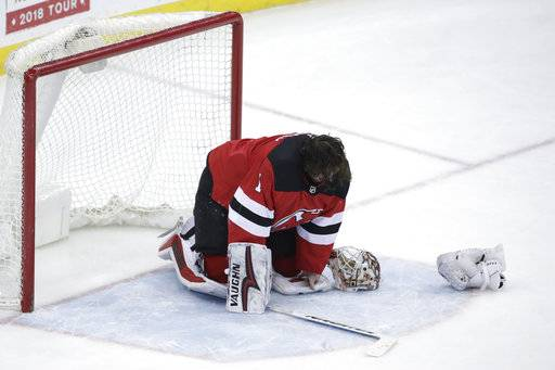 New Jersey Devils goalie Keith Kinkaid is slow to get up after taking a hit during the third period of the team's NHL hockey game against the Pittsburgh Penguins, Saturday, Feb. 3, 2018, in Newark, N.J. The Devils won 3-1.