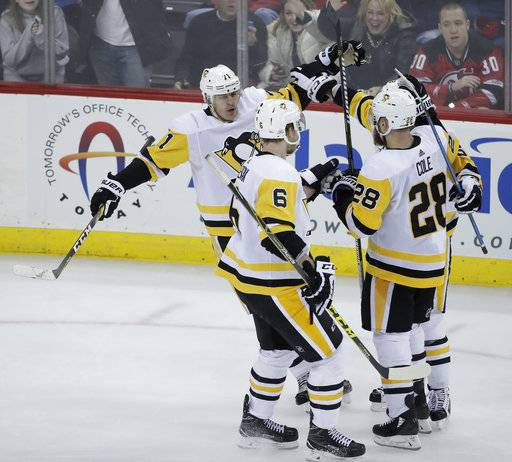 Pittsburgh Penguins celebrate a goal by center Evgeni Malkin, of Russia, (71) during the third period of an NHL hockey game against the New Jersey Devils, Saturday, Feb. 3, 2018, in Newark, N.J. The Devils won 3-1.