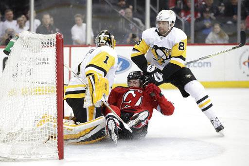 New Jersey Devils left wing Miles Wood, center, collides with Pittsburgh Penguins goaltender Casey DeSmith (1) and defenseman Brian Dumoulin (8) during the second period of an NHL hockey game Saturday, Feb. 3, 2018, in Newark, N.J.