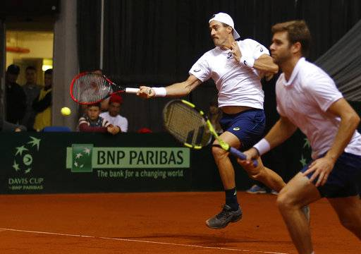 United States' Steve Johnson hits a forehand to Serbia's Nikola Milojevic and Miljan Zekic during their Davis Cup World Group first round tennis match in Nis, Serbia, Saturday, Feb. 3, 2018. At right is United States' Ryan Harrison.