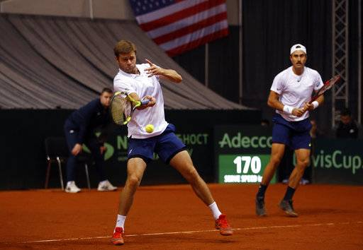 United States' Steve Johnson, right, watches teammate Ryan Harrison return the ball to Serbia's Nikola Milojevic and Miljan Zekic during their Davis Cup World Group first round tennis match in Nis, Serbia, Saturday, Feb. 3, 2018.