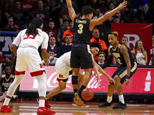 Rutgers guard Geo Baker, center bottom, loses the ball as he is defended by Purdue guard Carsen Edwards (3) and Vincent Edwards (12) during the first half of an NCAA college basketball game Saturday, Feb. 3, 2018, in Piscataway, N.J.
