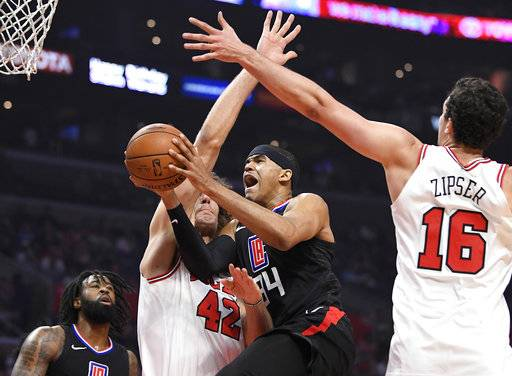 Los Angeles Clippers forward Tobias Harris, second from right, shoots as Chicago Bulls center Robin Lopez, second from left, and forward Paul Zipser, right, of Germany, defend while center DeAndre Jordan watches during the first half of an NBA basketball game, Saturday, Feb. 3, 2018, in Los Angeles.