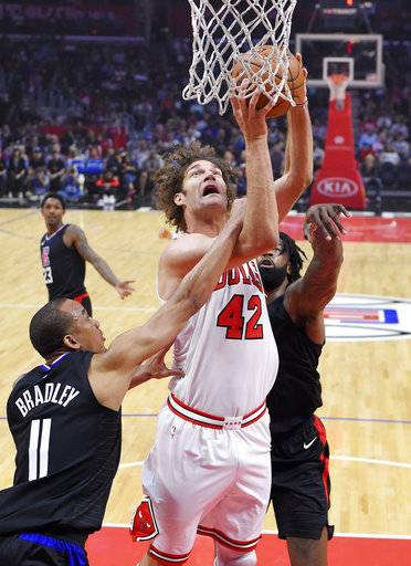 Chicago Bulls center Robin Lopez, center, shoots as Los Angeles Clippers guard Avery Bradley, left, and center DeAndre Jordan defend during the first half of an NBA basketball game, Saturday, Feb. 3, 2018, in Los Angeles.