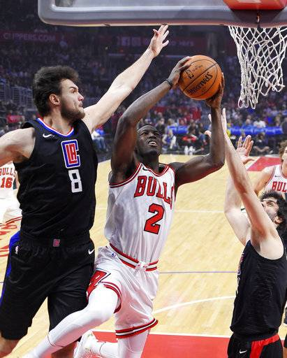 Chicago Bulls guard Jerian Grant, center, shoots as Los Angeles Clippers forward Danilo Gallinari, left, of Italy, and guard Milos Teodosic, of Serbia, defend during the first half of an NBA basketball game, Saturday, Feb. 3, 2018, in Los Angeles.