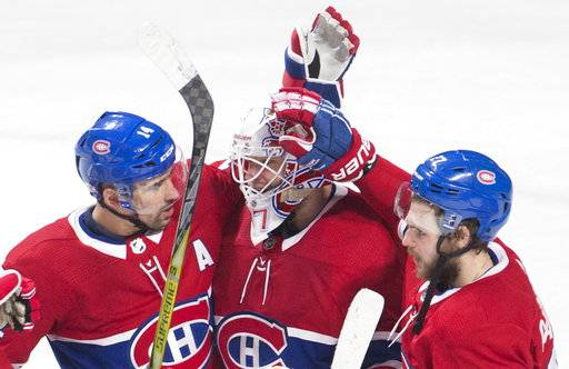 Montreal Canadiens goaltender Antti Niemi (37) celebrates with teammates Tomas Plekanec (14) and Alex Galchenyuk (27) after defeating the Anaheim Ducks 5-2 in an NHL hockey game in Montreal, Saturday, Feb. 3, 2018. (Graham Hughes/The Canadian Press via AP)