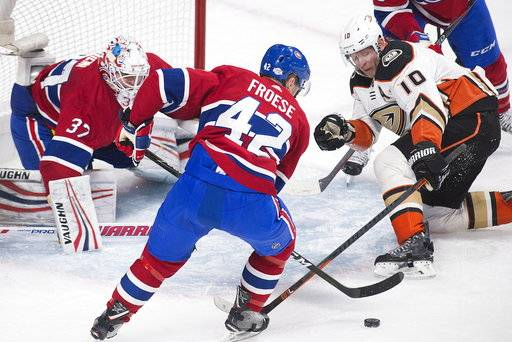 Anaheim Ducks right wing Corey Perry (10) moves in on Montreal Canadiens goaltender Antti Niemi (37) as center Byron Froese (42) defends during the second period of an NHL hockey of an NHL hockey game in Montreal, Saturday, Feb. 3, 2018. (Graham Hughes/The Canadian Press via AP)