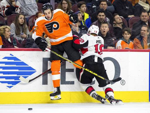 Philadelphia Flyers' Brandon Manning, left, reacts to colliding into the boards with Ottawa Senators' Tom Pyatt, right, during the third period of an NHL hockey game, Saturday, Feb. 3, 2018, in Philadelphia. The Senators won 4-3 in a shootout.