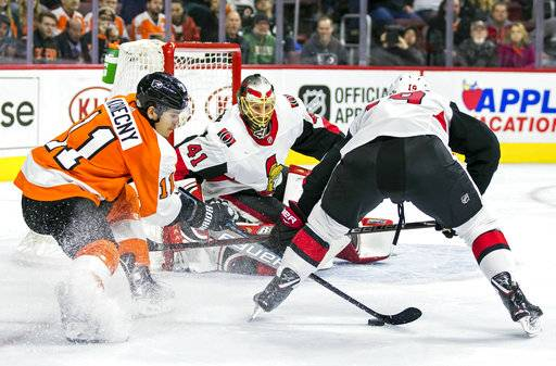 Philadelphia Flyers' Travis Konecny, left, tries to get the puck away from Ottawa Senators' Derick Brassard, right, in front of Senators' goalie Craig Anderson, center, during the second period of an NHL hockey game, Saturday, Feb. 3, 2018, in Philadelphia.