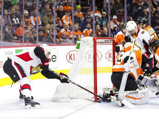 Ottawa Senators' Derick Brassard, left, slips the puck past Philadelphia Flyers' Alex Lyon, right, from behind for a goal during the first period of an NHL hockey game, Saturday, Feb. 3, 2018, in Philadelphia.