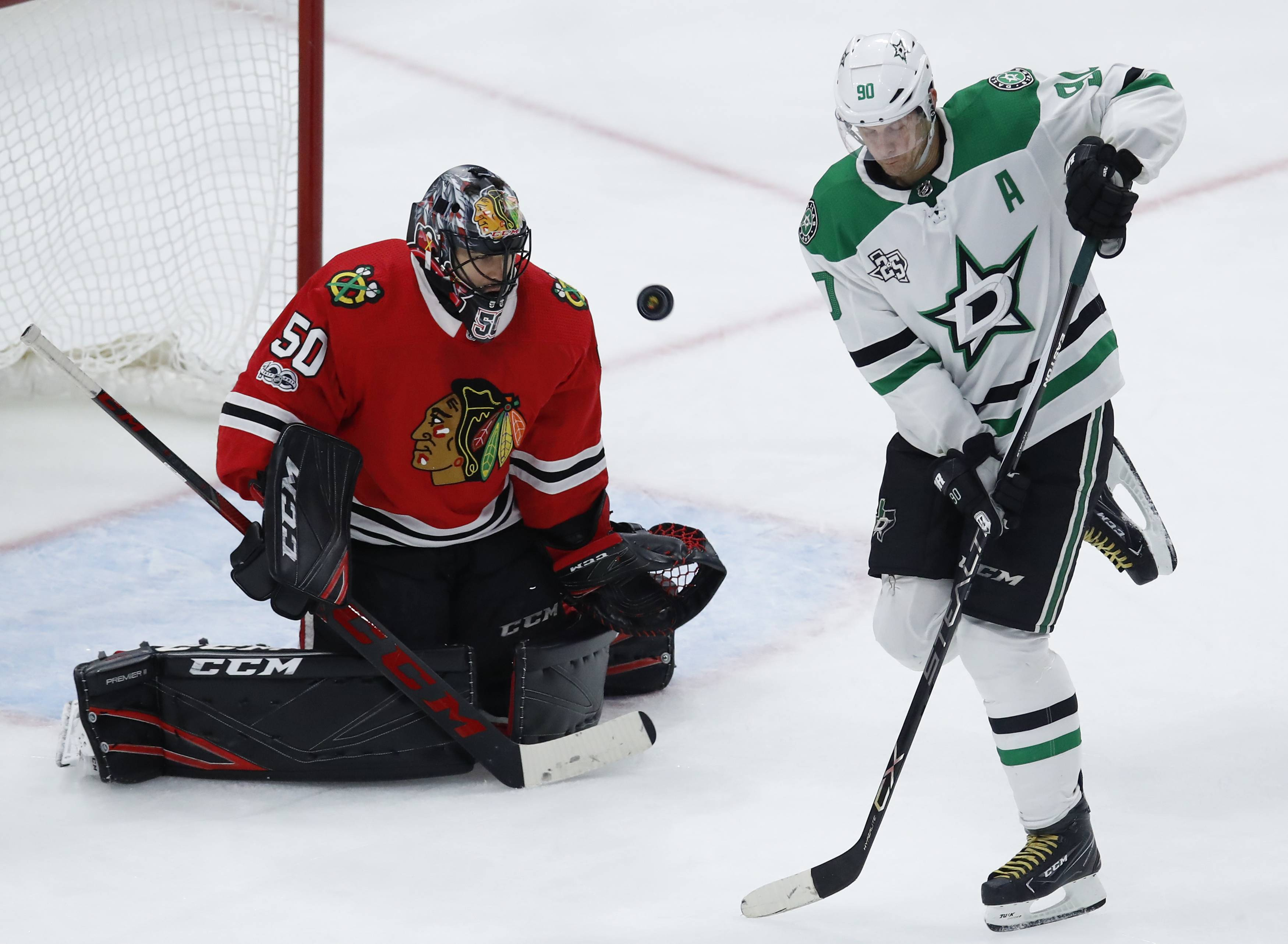 Chicago Blackhawks' Corey Crawford, left, was able to get on the ice Saturday morning after being on injured reserve since Dec. 27. The team was hopeful he would be able to do the same on Sunday, but his overall status is still unknown.