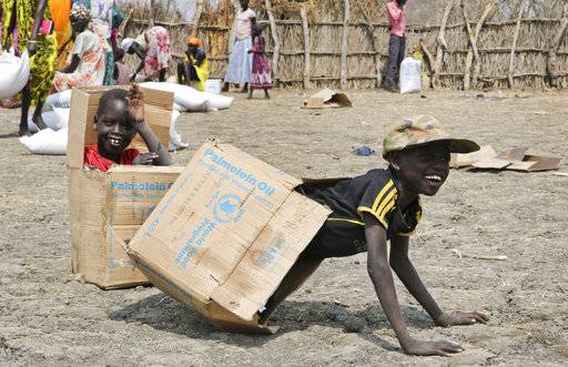In this photo taken Saturday, Jan. 20, 2018, children play in empty cardboard boxes during a food distribution by Oxfam outside Akobo town, one of the last rebel-held strongholds in South Sudan. Child abductions have risen during South Sudan's civil war as desperate people try to make a living, and one child, no matter the age, is said to sell for 20 cows, worth about $7,000.
