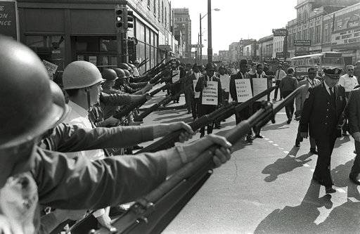 FILE-In this March 29, 1968 file photo, striking Memphis sanitation workers march past Tennessee National Guard troops with fixed bayonets during a 20-block march to City Hall in Memphis, Tenn. Fifty years ago, two sanitation workers were killed by a malfunctioning garbage truck in Memphis. Martin Luther King Jr. came to Memphis to support the strike, a move that cost him his life when he was fatally shot on the balcony of a Memphis hotel on April 4, 1968.