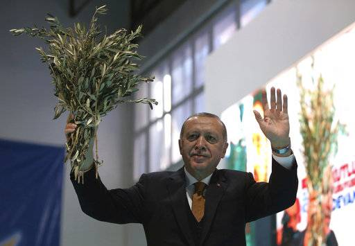 Turkey's President Recep Tayyip Erdogan holds olive branches as he addresses his party members in Batman, Turkey, Saturday, Feb. 3, 2018. The Turkish military says two of its soldiers have been killed in Syria and a third was killed on the Turkish side of the border in an attack by Syrian Kurdish militiamen.(Murat Cetinmuhurdar/Pool Photo via AP)