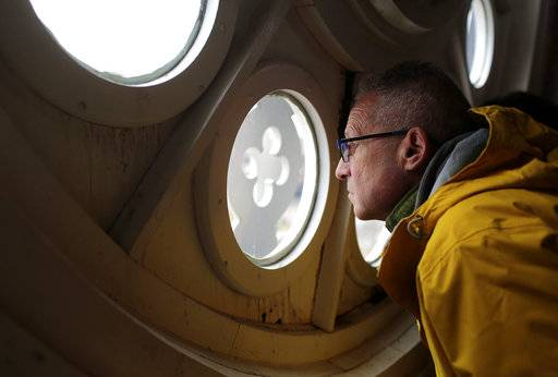In this Jan. 28, 2018 photo, Jessie Lasky, peers through one of the openings in the clock face in the tower building while on a tour of it on Arsenal Island of the Clock Tower building on Arsenal Island, in Rock Island, Ill. The Army Corps of Engineers' logistics office is working to repair the clock.  It serves as the headquarters for the Corps' Rock Island District. Free tours are offered at the two-story-tall room that houses the 1867 clock. (Brian Achenbachr/QConline.com via AP)