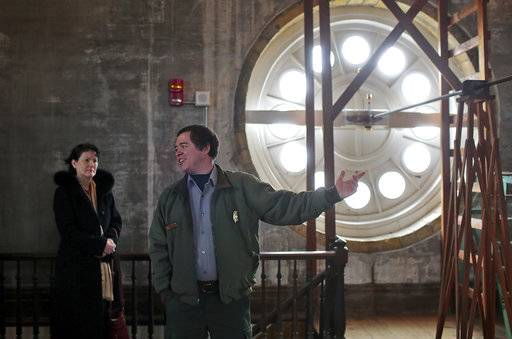 In this Jan. 28, 2018 photo, Terri Hoogheem, left, listens as park ranger Mike McKean shares information about the inner workings of the room and the clockwork on a tour of the Clock Tower building on Arsenal Island, in Rock Island, Ill. The Army Corps of Engineers' logistics office is working to repair the clock.  It serves as the headquarters for the Corps' Rock Island District. Free tours are offered at the two-story-tall room that houses the 1867 clock. (Brian Achenbachr/QConline.com via AP)