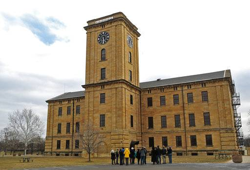 In this Jan. 28, 2018 photo, a group stands outside the Clock Tower building on their way inside for a tour of it as well as some eagle watching from the tower on Arsenal Island in Rock Island, Ill. The Army Corps of Engineers' logistics office is working to repair the clock.  It serves as the headquarters for the Corps' Rock Island District. Free tours are offered at the two-story-tall room that houses the 1867 clock. (Brian Achenbachr/QConline.com via AP)
