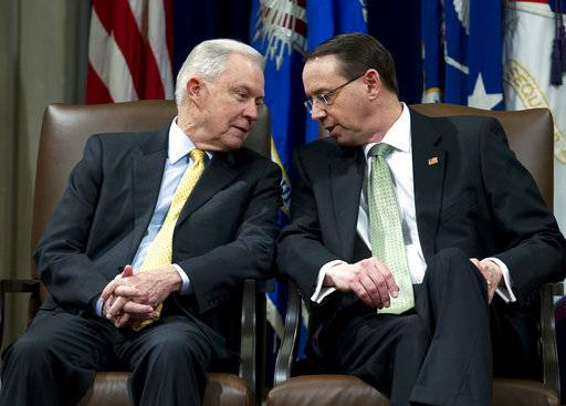 Attorney General Jeff Sessions speaks with Deputy Attorney General Rod Rosenstein, during the opening of the summit on Efforts to Combat Human Trafficking at Department of Justice in Washington, Friday, Feb. 2, 2018. President Donald Trump, dogged by an unrelenting investigation into his campaign's ties to Russia, lashes out at the FBI and Justice Department as politically biased ahead of the expected release of a classified Republican memo criticizing FBI surveillance tactics.