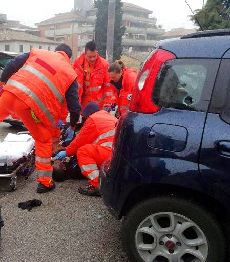 Italian Paramedics a wounded man after a shooting broke out in Macerata, Italy, Saturday, Feb. 3, 2018. A lone gunman opened fire on foreigners in drive-by shootings in a central Italian city, wounding an undisclosed number of people Saturday morning before being arrested, police said. The suspect's motive wasn't immediately clear, but the city of Macerata is still reeling from the gruesome killing of a young Italian woman this week, allegedly at the hands of a Nigerian immigrant. (Guido Picchio/ANSA via AP)