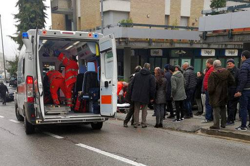 Paramedics, background center, attend a wounded man after a shooting broke out in Macerata, Italy, Saturday, Feb. 3, 2018. Italian police arrested a lone gunman in a series of drive-by shootings targeting foreigners Saturday morning that paralyzed a small central Italian city still reeling from the gruesome murder of a young Italian woman allegedly at the hands of a Nigerian immigrant.  (Guido Picchio/ANSA via AP)