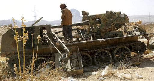 In this Friday, Feb. 2, 2018, photograph, a Yemeni militiaman allied to the country's internationally recognized government looks over the wreckage of a destroyed piece of mobile artillery on the outskirts of Sanaa, Yemen. Yemen's conflict, which began as a civil war in 2014 and escalated into a regional proxy fight, drags on today. Winning the hardscrabble terrain takes time and costs dearly, only exacerbating the country's humanitarian crises and making a war that's seen over 10,000 people killed last that much longer.