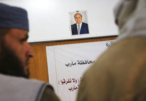 In this Saturday, Feb. 3, 2018, photograph, an official portrait of Yemen's internationally recognized President, Abed Rabbo Mansour Hadi, hangs above Muslim clerics gathered for a meeting in Marib, Yemen. Yemen's conflict, which began as a civil war in 2014 and escalated into a regional proxy fight, drags on today. Winning the hardscrabble terrain takes time and costs dearly, only exacerbating the country's humanitarian crises and making a war that's seen over 10,000 people killed last that much longer.