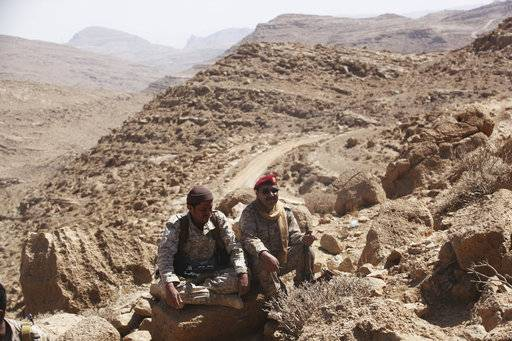 In this Friday, Feb. 2, 2018, photograph, two Yemeni soldiers allied to the country's internationally recognized government wait near the front line of the Yemen war on the outskirts of Sanaa, Yemen. Yemen's conflict, which began as a civil war in 2014 and escalated into a regional proxy fight, drags on today. Winning the hardscrabble terrain takes time and costs dearly, only exacerbating the country's humanitarian crises and making a war that's seen over 10,000 people killed last that much longer.