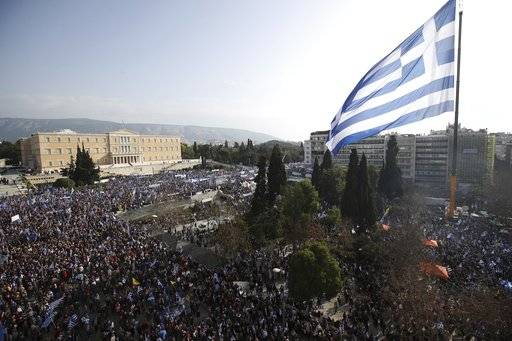 A giant Greek flag hangs from a crane waves over protesters during a rally in Athens, Sunday, Feb. 4, 2018. Protesters from across Greece were thronging the Greek capital's main square outside parliament Sunday to protest a potential Greek compromise in a dispute with neighboring Macedonia over the former Yugoslav republic's official name.